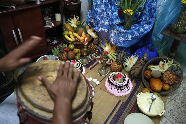 Musicians play drums in front of an altar during a santeria ceremony for the Afro-Cuban deity Yemaya in Havana, Cuba, Thursday, May 7, 2015. Afro-Cuban santeria is a fusion of African beliefs and Catholicism developed by African yoruba slaves in Cuba. (Photo by Desmond Boylan/AP Photo)