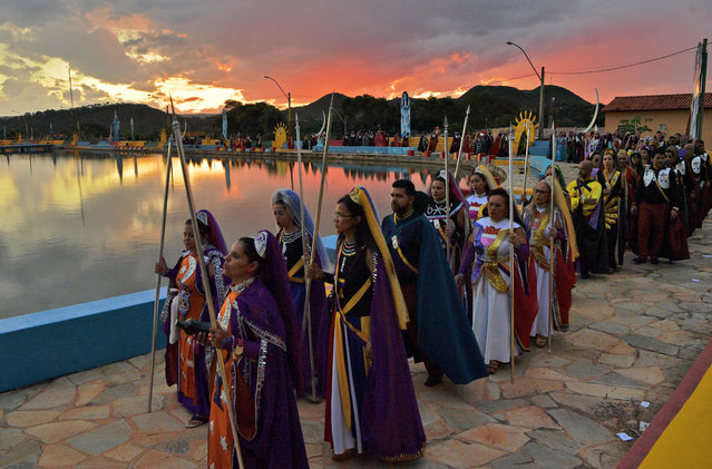 Devotees of the Vale do Amanhecer religious community take part in a ceremony at their temple complex in Vale do Amanhecer (Sunrise Valley), a community on the outskirts of Planaltina, 50 km from the Brazilian capital, Brasilia, on April 30, 2019. This eclectic community holds its most important ritual of the year on Labour Day to honour the mediums who communicate with good and bad spirits. The group combines a range of religious practices, including Christian and Hindu, with symbols borrowed from the Incas and Mayans, as well as a belief in extraterrestrial life and intergalactic travel. With some 600 temples throughout Brazil, Portugal, Germany, Japan, Bolivia, Uruguay and the United States, the religious movement claims to have 800,000 members. (Photo by Carl De Souza/AFP Photo)