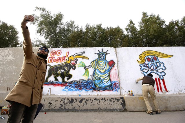 Iraqi men take pictures near a mural featuring anti-US President Donald Trump slogans, in Basra, southeast of Baghdad, Iraq February 2, 2017. (Photo by Essam Al-Sudani/Reuters)