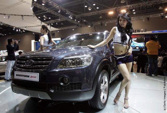 Models poses next to a GM Daewoo Motor's Winstorm Sport car