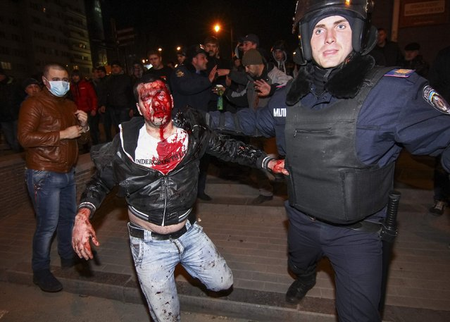 A police officer escorts a wounded participant of an anti-war rally during clashes with pro-Russian demonstrators in Donetsk March 13, 2014. One person was killed and several were treated for injuries in hospital on Thursday when hundreds of Ukrainian demonstrators clashed in the eastern city of Donetsk, the local health authority said. (Photo by Reuters/Stringer)