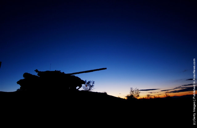 Pre-dawn glow silhouettes a tank on display at the entrance to the U.S. Armys Fort Irwin Military Reserve