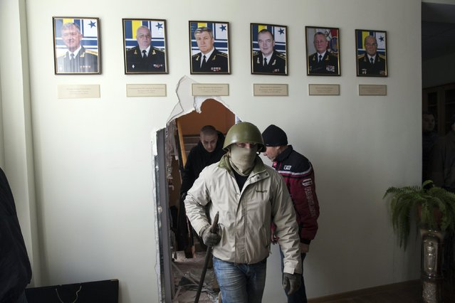 A pro-Russian supporter walks through a wall after breaking into the territory of the naval headquarters in Sevastopol, March 19, 2014. (Photo by Baz Ratner/Reuters)