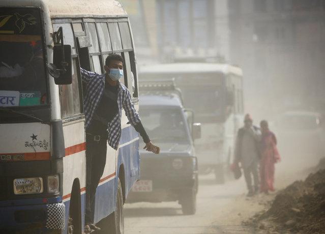 A bus conductor wearing a mask hangs onto a bus as he travels through a dusty road in Kathmandu, Nepal February 27, 2017. (Photo by Navesh Chitrakar/Reuters)