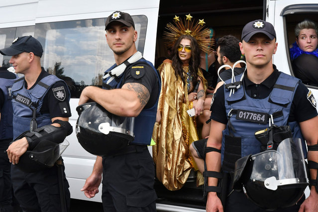 A participant looks around while sitting in a bus as policemen stand guard during the annual Gay Pride parade in Kiev on June 23, 2019. (Photo by Genya Savilov/AFP Photo)