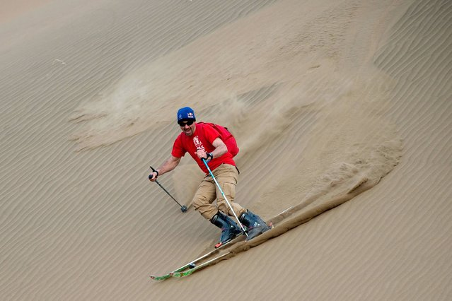 This picture taken on April 20, 2016 shows French former overall Ski World Cup winner and race car driver Luc Alphand skiing down a big sand dune during an off-road mapping recognition excercise ahead of the Silk Way Rally 2016 in the Gobi desert, some 2,000 kms (1250 miles) northwest of Beijing. The 2016 Silk Way Rally takes place in July and will see competitors race from Moscow's Red Square to the Chinese capital Beijing. (Photo by Nicolas Asfouri/AFP Photo)
