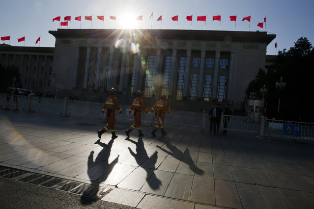 In this photo taken Thursday, March 9, 2017, fire fighters march in front of the Great Hall of the People where a plenary session of the Chinese People's Political Consultative Conference is held in Beijing. (Photo by Ng Han Guan/AP Photo)