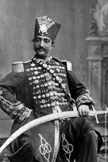 circa 1880:  Nasiruddin, Shah of Persia (Iran) in regal attire, with his scimitar