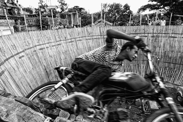 "Action Hero. As part of a show called ""Well of Death"", a biker performs a stunt at a village fair to celebrate Rath Jatra, a Hindu festival. Dhamrai, Bangladesh. (Photo by Nidal Adnan Kibria/Smithsonian.com)"