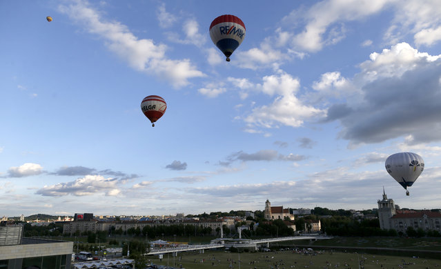 Hot air balloons fly near Neris river in the center of Vilnius, Lithuania, Tuesday, June 30, 2015. (Photo by Mindaugas Kulbis/AP Photo)