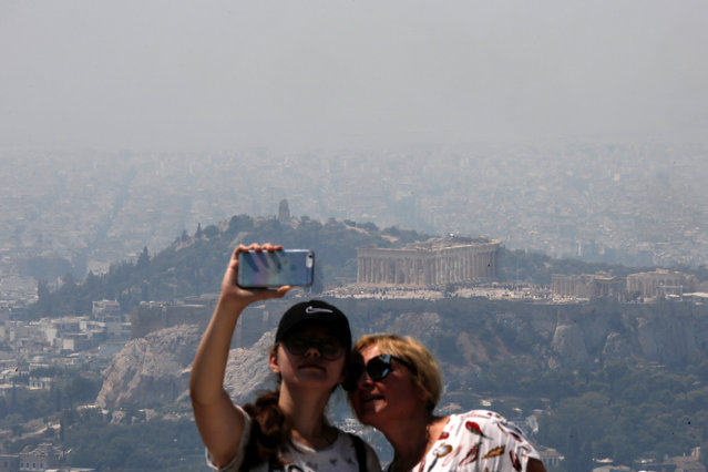 Tourists take photos as the Parthenon temple sits atop the Acropolis hill amidst thick smoke from a wildfire burning at the island of Evia some 70 km north of Athens, Greece, 13 August 2019. (Photo by Kostas Tsironis/EPA/EFE)
