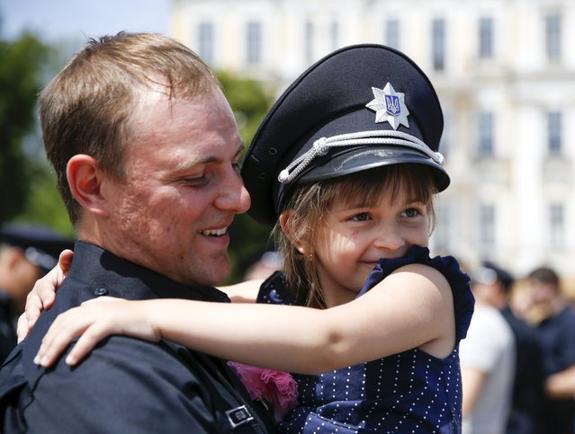 A police officer holds his daughter after an oath-taking ceremony, which started up the work of a new police patrol service, part of the Interior Ministry reform initiated by Ukrainian authorities, in Kiev, Ukraine, July 4, 2015. (Photo by Valentyn Ogirenko/Reuters)