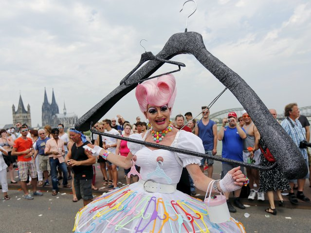 A reveller takes part in the annual Christopher Street Day gay parade (CSD) with a huge home-made coat-hanger costume in front of the Cologne cathedral, western Germany, July 5, 2015. (Photo by Fabrizio Bensch/Reuters)