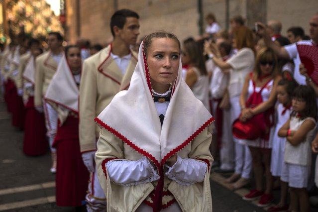 Revelers wearing a local traditional outfit march during the San Fermin procession in Pamplona, Spain, Tuesday, July 7, 2015. (Photo by Andres Kudacki/AP Photo)