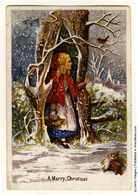 1872: A Christmas greetings card showing a girl in a red cape sheltering from the snow in a hollow tree