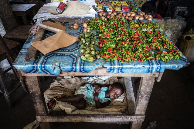 A child sleeps under a table at the Jorkpan market in Sinkor district in Monrovia, on May 2, 2016. (Photo by Marco Longari/AFP Photo)