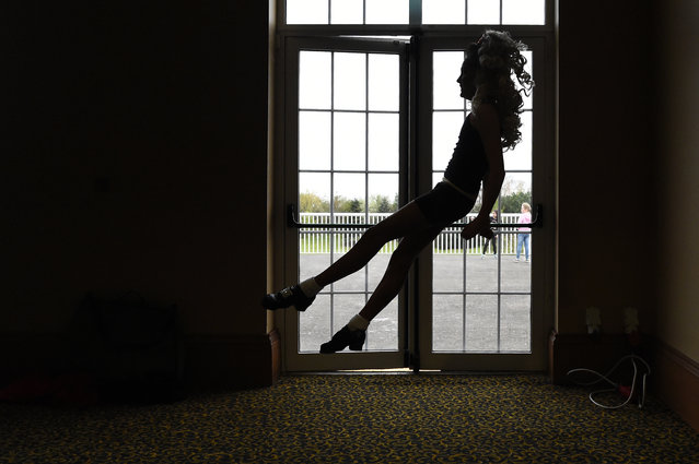 A dancer warms up backstage before performing during the World Irish Dancing Championships in Dublin, Ireland on April 11, 2017. The April 9-16 event draws some 5,000 performers from Ireland and overseas, including from both the Irish diaspora in places like the United States and Australia as well as less likely countries such as Russia and Japan. Contestants range in age from eight to 30, according to the organisers. Excitement was palpable backstage on Tuesday as performers warmed up for the championships' categories including the traditional solo step dances, figure choreography team dancing, dance drama that tells a story and ceili, a kind of Celtic square dance. For many of the young female dancers, the day began with a 45-minute long make-up session to ensure their colourful dresses, curled wigs and rhinestone tiaras sat just right. In the course of the week, some 25,000 spectators are expected at the event, cheering on the competitors. (Photo by Clodagh Kilcoyne/Reuters)