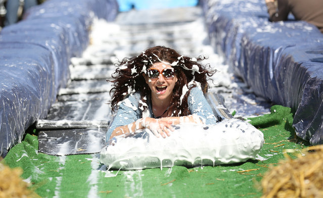 A participant on a lilo slides down a giant water slide that has been installed down Park Street on May 4, 2014 in Bristol, England. (Photo by Matt Cardy/Getty Images)