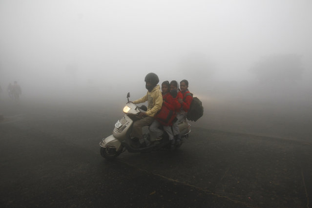 Schoolgirls ride on a scooter on a foggy winter morning in New Delhi December 17, 2013. (Photo by Anindito Mukherjee/Reuters)