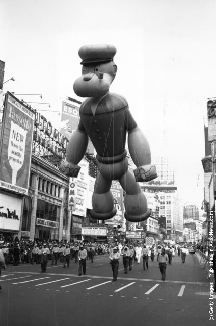 A giant inflatable Popeye floating over Times Square, New York, during a Thanksgiving Parade, 1961