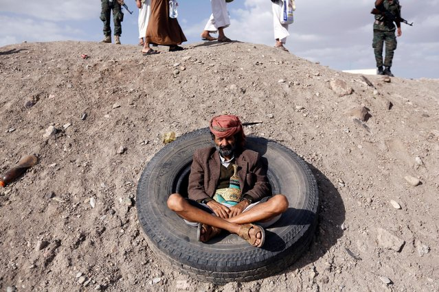 A tribesman loyal to the Houthi movement sits inside a used tyre as he watches a demonstration against the U.S. intervention in Yemen, in the country's capital Sanaa, May 13, 2016. (Photo by Khaled Abdullah/Reuters)