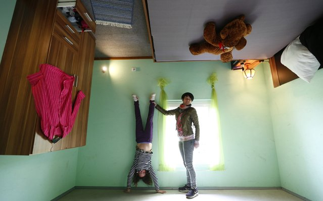 """Dutch tourists Rosanna (R) and Nova pose for a photograph inside the bedroom of the """"Crazy House"""", which is completely built upside-down, in the village of Affoldern near the Edersee lake, May 7, 2014. Three friends came up with the idea to build the tourist attraction, which cost about 200,000 euros and took some six weeks to complete. (Photo by Kai Pfaffenbach/Reuters)"""