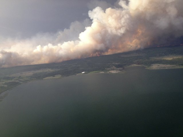 Smoke rises from a 7,000 hectare (17,000 acre) fire on the north side of Puntzi Lake, British Columbia in a picture release by the BC Wildfire Service July 11, 2015. The area is subject to an evacuation order. (Photo by Reuters/BC Wildfire Service)