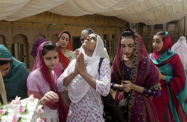 A Sikh pilgrim (C) prays with others inside the compound of Maharaja Ranjit Singh's mausoleum in Lahore, Pakistan, June 29, 2015. Hundreds of Sikh pilgrims attended the ceremonies to commemorate 176th death anniversary of Singh. Singh was a former Sikh ruler of the united Punjab region under British colonial rule. (Photo by Mohsin Raza/Reuters)
