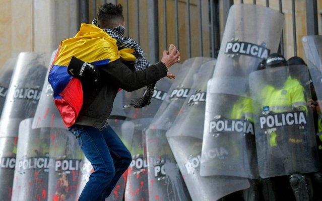 A University student throws a stone at riot police during a protest to demand better funding for education in Bogota on October 10, 2019. (Photo by Raul Arboleda/AFP Photo)