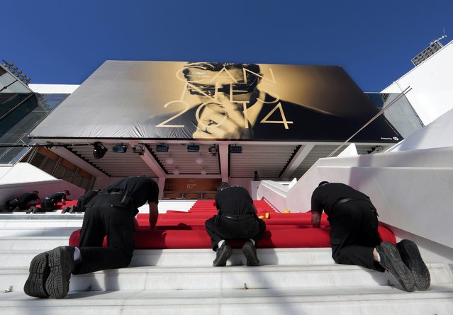 Workers install the red carpet in front of the main entrance of the Festival Palace for the opening ceremony of the 67th Cannes Film Festival in Cannes May 14, 2014. The festival will run from May 14 to 25. (Photo by Eric Gaillard/Reuters)
