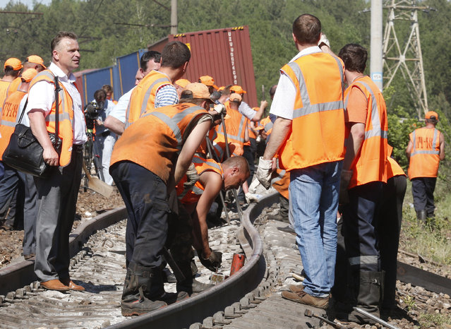 Employees of repair services work at the site of a train collision in Moscow region May 20, 2014. A passenger train on its way to Moldova collided with a freight train near Moscow on Tuesday, killing at least four people and injuring 15, a spokeswoman for Russia's Emergencies Ministry said. The reason for the collision, near the town of Naro-Fominsk 55 km (34 miles) southwest of Moscow, was not immediately clear. (Photo by Grigory Dukor/Reuters)