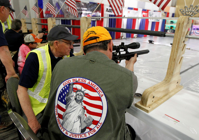 Gun instructor Robert Allen (L) works with gun enthusiasts at the air gun range at the National Rifle Association's annual meetings and exhibits show in Louisville, Kentucky, May 21, 2016. (Photo by John Sommers II/Reuters)