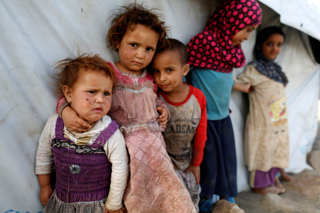 Children stand next to a tent at a camp for people displaced by the war near Sanaa, Yemen April 24, 2017. (Photo by Khaled Abdullah/Reuters)