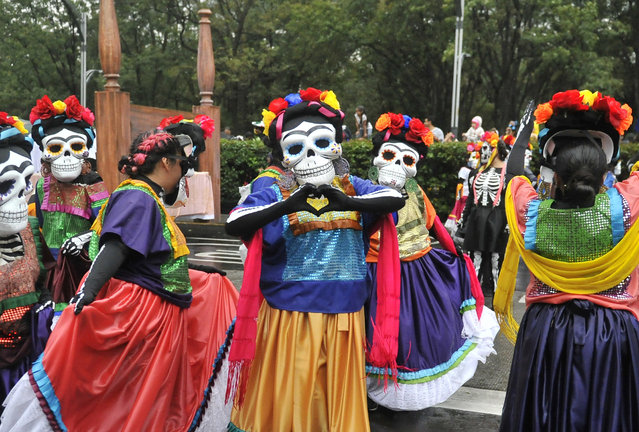People take part in the Day of the Dead parade along Reforma avenue in Mexico City, on October 27, 2019. (Photo by Claudio Cruz/AFP Photo)