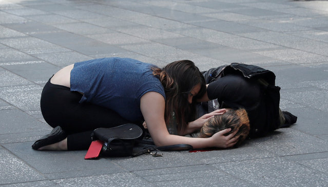 A woman attends to an injured man on the sidewalk in Times Square after a speeding vehicle struck pedestrians on the sidewalk in New York City, May 18, 2017. (Photo by Mike Segar/Reuters)