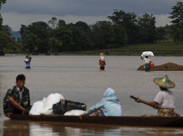 A family wades through flooded waters at Kawlin township, Sagaing division, Myanmar July 22, 2015. Heavy rains caused flooding over 20,000 acres of rice field and in about a hundred villages, killing at least eight people, according to local media. (Photo by Soe Zeya Tun/Reuters)