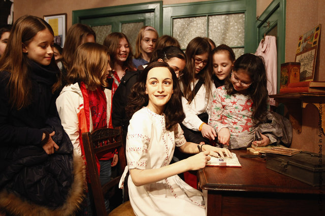 Childrens watch the wax figure of Anne Frank and their hideout reconstruction at Madame Tussauds in Berlin, Germany