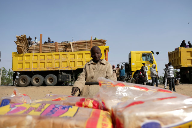 A refugee boy selling loaves of bread pushes his cart past trucks full of people in the Muna Garage Maiduguri, Nigeria February 16, 2017. (Photo by Paul Carsten/Reuters)