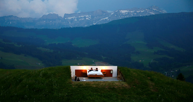 Raphael and Mirjam (R) pose as first guests in the bedroom of the Null-Stern-Hotel (Zero-star-hotel) land art installation by Swiss artists Frank and Patrik Riklin on an alp mount Saentis near Gonten, Switzerland June 1, 2017. Guests can order overnight stays in the Null-Stern-hotelroom with no walls and roof located on some 1,200 metres (3,937 ft) altitude in the eastern Swiss Alps. (Photo by Arnd Wiegmann/Reuters)