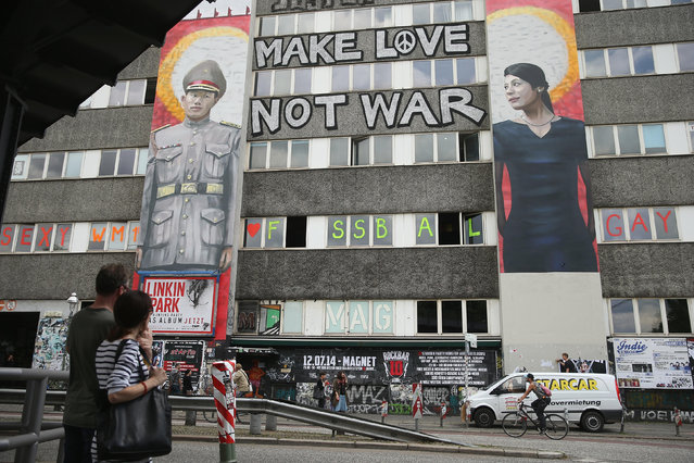 A couple stop to look at two murals of street art in Kreuzberg district on June 26, 2014 in Berlin, Germany. Berlin, with its long tradition of counter-culture, has become a mecca for street art of all dimensions and messages. (Photo by Sean Gallup/Getty Images)