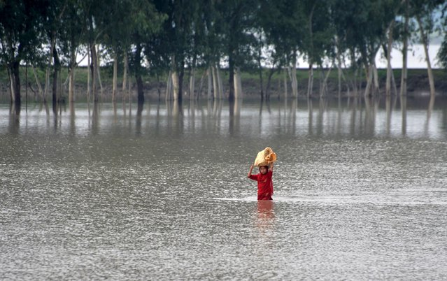 A girl walks through a flooded street at Camp Koruna area of Nowshera District, northwestern Pakistan, August 3, 2015. (Photo by Khuram Parvez/Reuters)