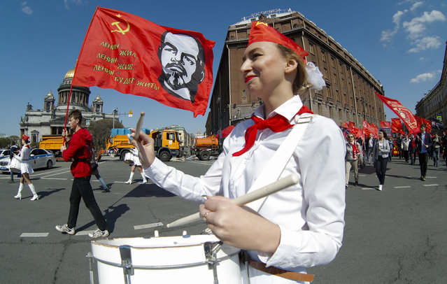 Communist party supporters march with a flag depicting Soviet Union founder Lenin during a May Day rally in St.Petersburg, Russia, Wednesday, May 1, 2019. (Photo by Dmitri Lovetsky/AP Photo)
