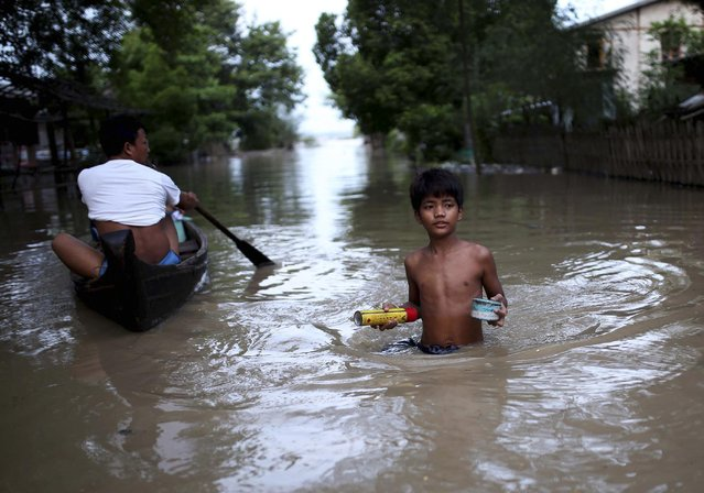 In this August 3, 2015, photo, residents make their way through floodwaters in Minbu, Magway division, in Myanmar. The Ministry of Social Welfare, Relief and Resettlement said that more than 200,000 people are affected in 11 of the country's 14 states and divisions by flooding. In addition to damage to houses and farmland, infrastructure has been very badly hit, with roads and rail lines cut in many places and telecommunication links broken. (Photo by Hkun Lat/AP Photo)