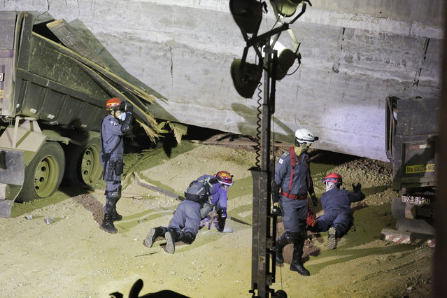 Fire department personnel look underneath a bridge that collapsed in Belo Horizonte, Brazil, Thursday, July 3, 2014. The overpass under construction collapsed Thursday in the Brazilian World Cup host city. The incident took place on a main avenue, the expansion of which was part of the World Cup infrastructure plan but, like most urban mobility projects related to the Cup, was not finished on time for the event. (Photo by Victor R. Caivano/AP Photo)