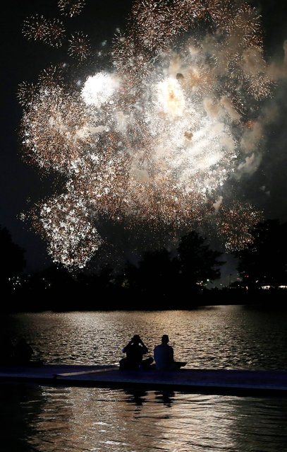Fireworks explode over the Charles River in Boston, Thursday, July 3, 2014. The annual Boston Pops Fourth of July concert and fireworks show was moved up a day because of potential heavy rain ahead of Hurricane Arthur. (Photo by Michael Dwyer/AP Photo)