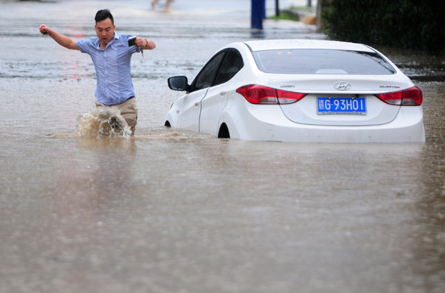 A picture made available on 20 June 2016 shows a driver leaving his car in the flood in Jiujiang, Jiangxi Province, China, 19 June 2016. A week of torrential rain in southern China has killed dozens of people and forced relocation of tens of thousands of residents, media reported. (Photo by Hu GuolinEPA)