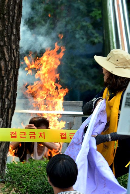 A man sets himself on fire during a weekly anti-Japan rally to demand for an official apology and compensation from the Japanese government in front of the Japanese embassy in Seoul, South Korea, August 12, 2015. A South Korean man set himself on fire on Wednesday at a protest in front of the Japanese embassy in Seoul, days before the Aug. 15th anniversary marking 70 years since the end of Japan's colonial occupation of the Korean peninsula. (Photo by Son Hyung-ju/Reuters/News1)