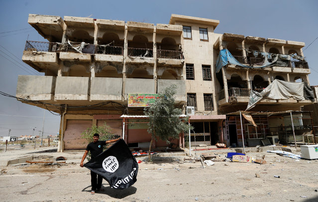A member of the Iraqi security forces holds an Islamist State flag, after pulling it down from a building, in Falluja, Iraq, June 25, 2016. (Photo by Thaier Al-Sudani/Reuters)