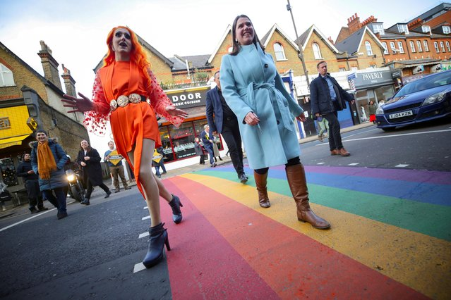 British opposition Liberal Democrats Party Leader Jo Swinson walks over a pedestrian crossing with a member of the LGBTQ community in Wimbledon, London, England, Wednesday, December 11, 2019 during the General Election campaign tour. Britain goes to the polls on Dec. 12. (Photo by Lisi Niesner/Reuters)