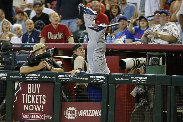Photographers try to avoid Chicago Cubs' Anthony Rizzo, after he made a diving catch into the photo well, on a foul ball hit by Arizona Diamondbacks' Aaron Hill during the sixth inning of a baseball game on Sunday, July 20, 2014, in Phoenix. (Photo by Ross D. Franklin/AP Photo)